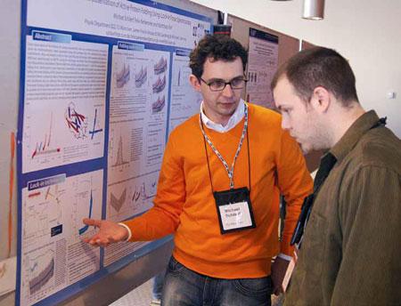Des étudiants au doctorat venant d'Allemagne et du Canada discutent de leurs recherches lors d'une séance de présentation par affiches.
